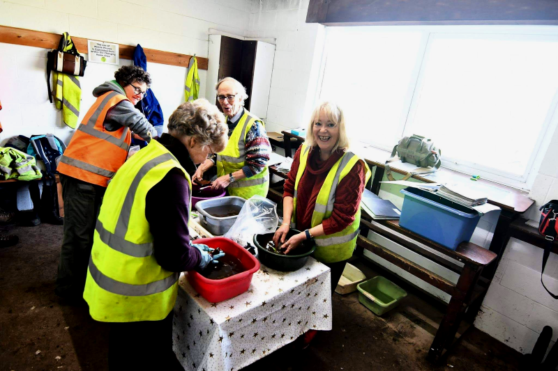 Volunteers hand-clean finds from the trenches outside   Photo © Wardell Armstrong