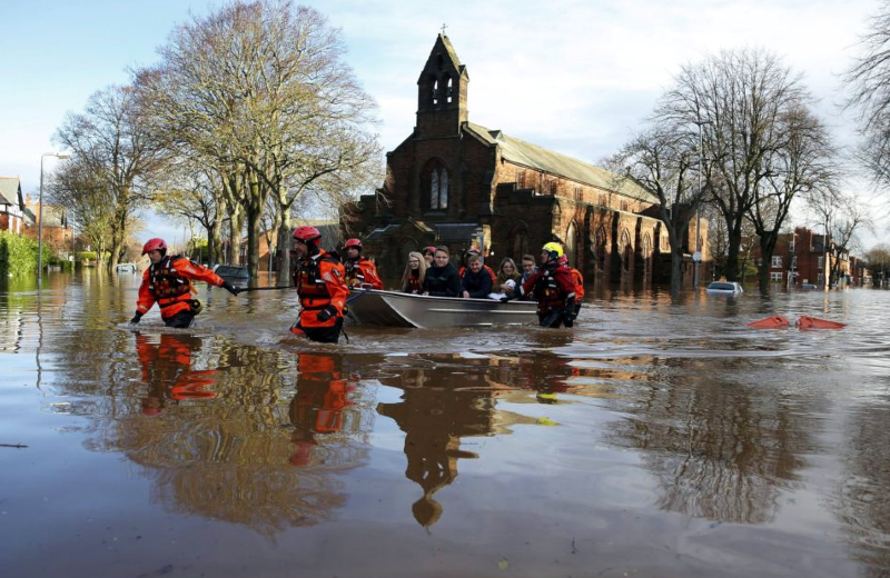 Rescue workers pull a boat full of residents along a flooded street in Carlisle on 6th December, after Storm Desmond   © Phil Noble / Reuters
