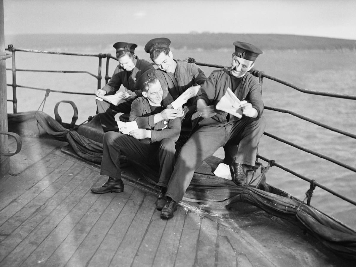 Sailors read their Christmas mail aboard HMS DUNLUCE CASTLE at Scapa Flow, December 1941 (A 13325)